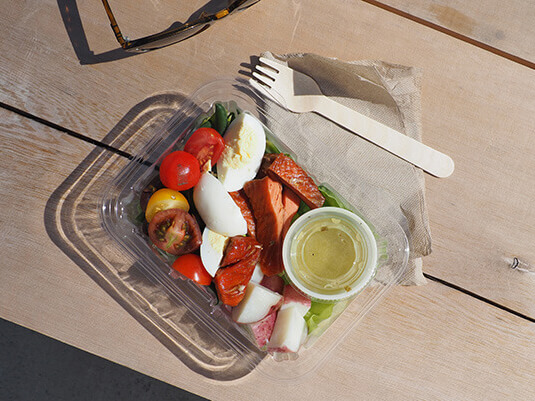 To-go salad container on a wooden table