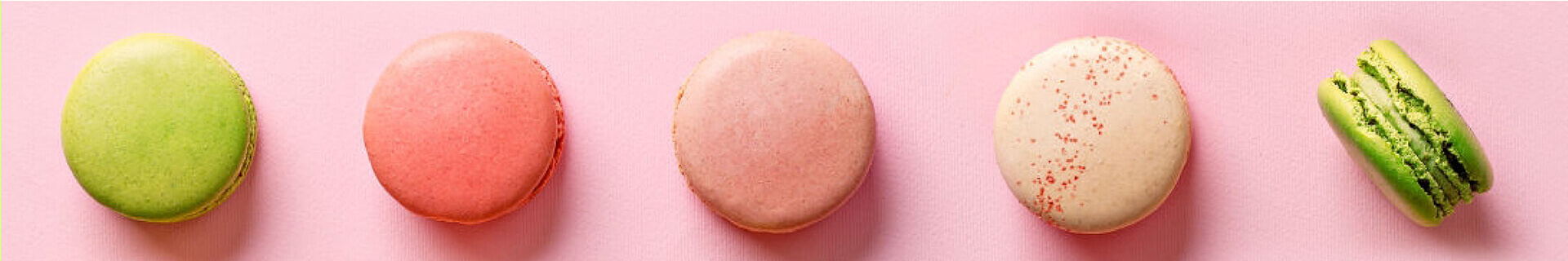 A row of five macarons on pink background