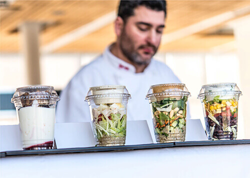 Salad cups with chef in the background