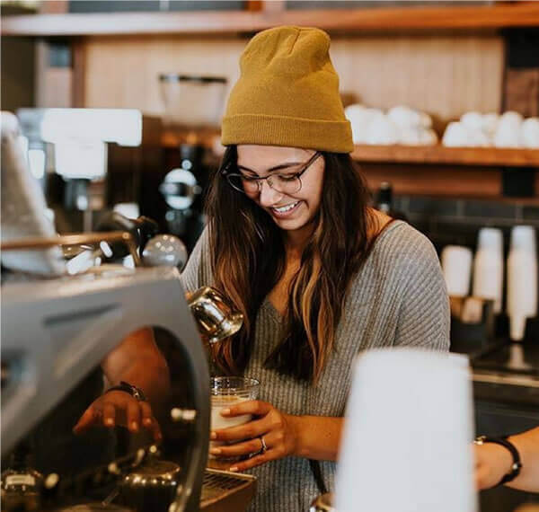 Female barista smiling pouring coffee