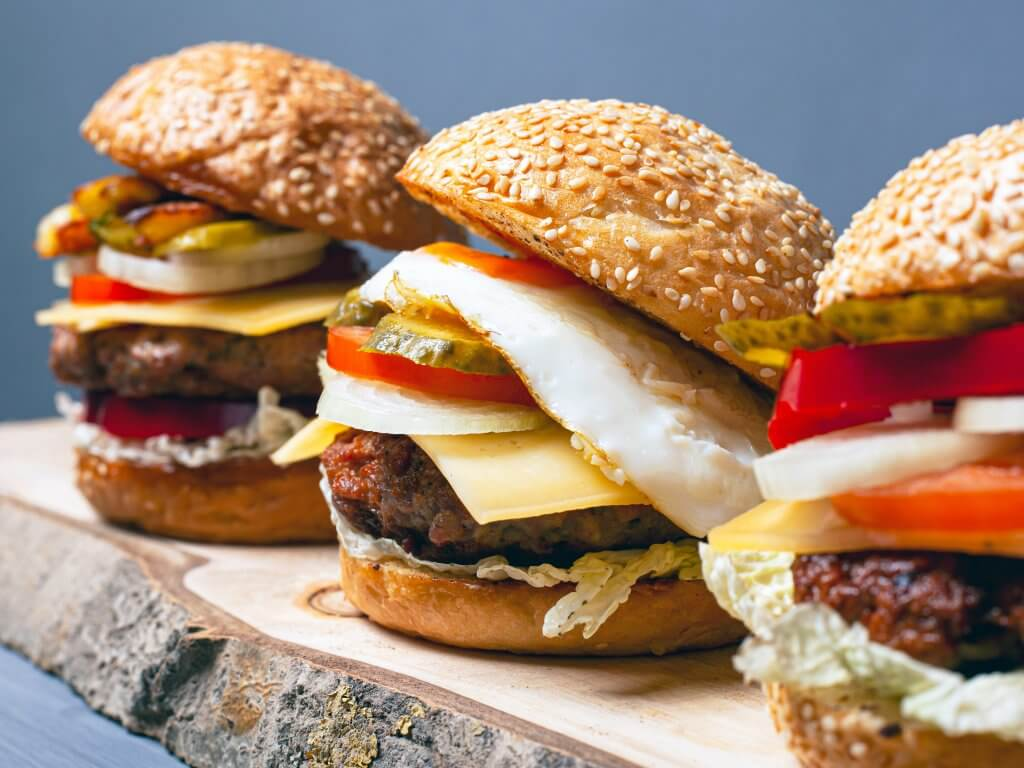 Three burgers on a wooden shelf