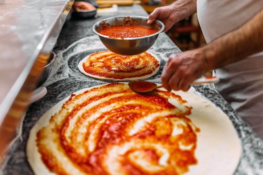 Man putting sauce on pizza dough