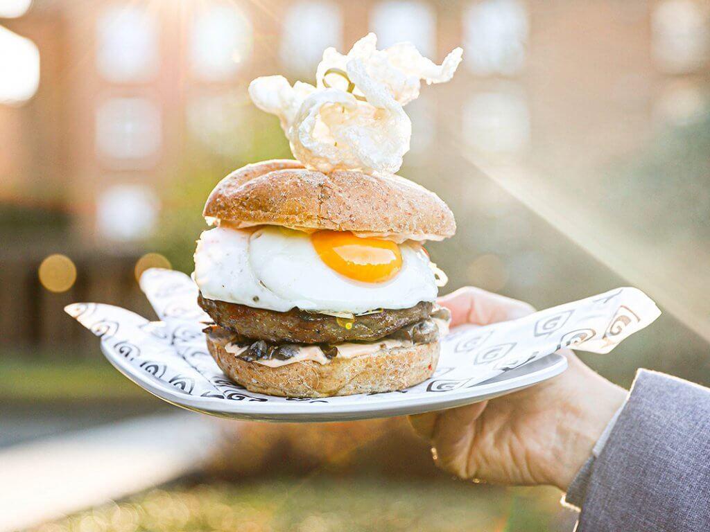 Person holding a breakfast sandwich