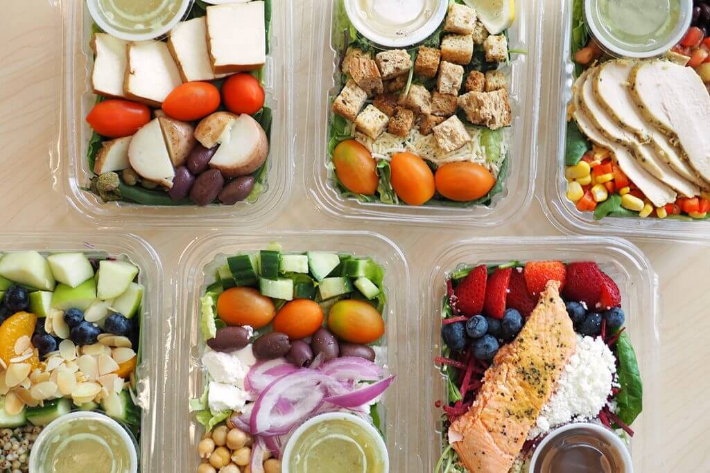 Various to-go containers of salad