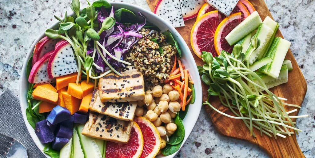 Salad bowl and wooden cutting board filed with fruits and vegetables