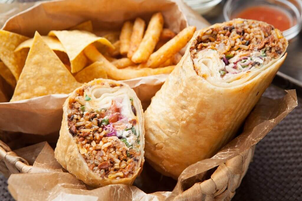 Burrito with fries and chips on table