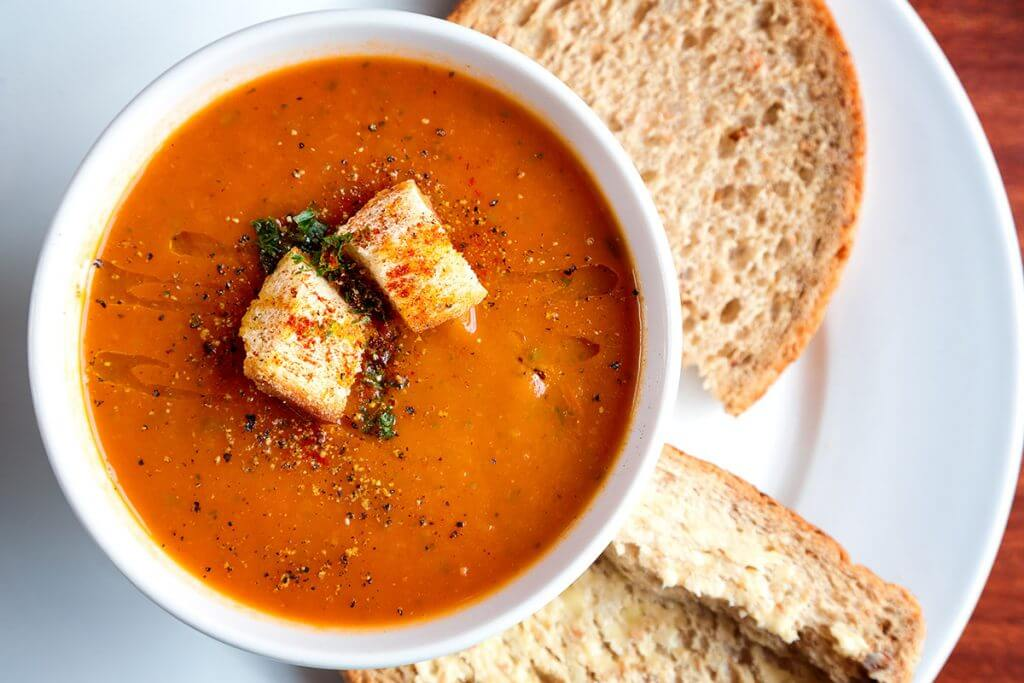 Soup with bread on a white glass plate