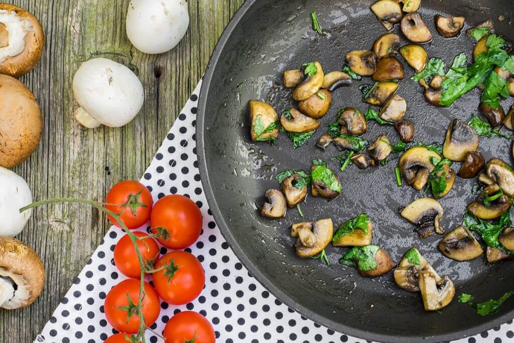 Cooked mushrooms in a pan with tomatoes and raw mushrooms spread out next to it