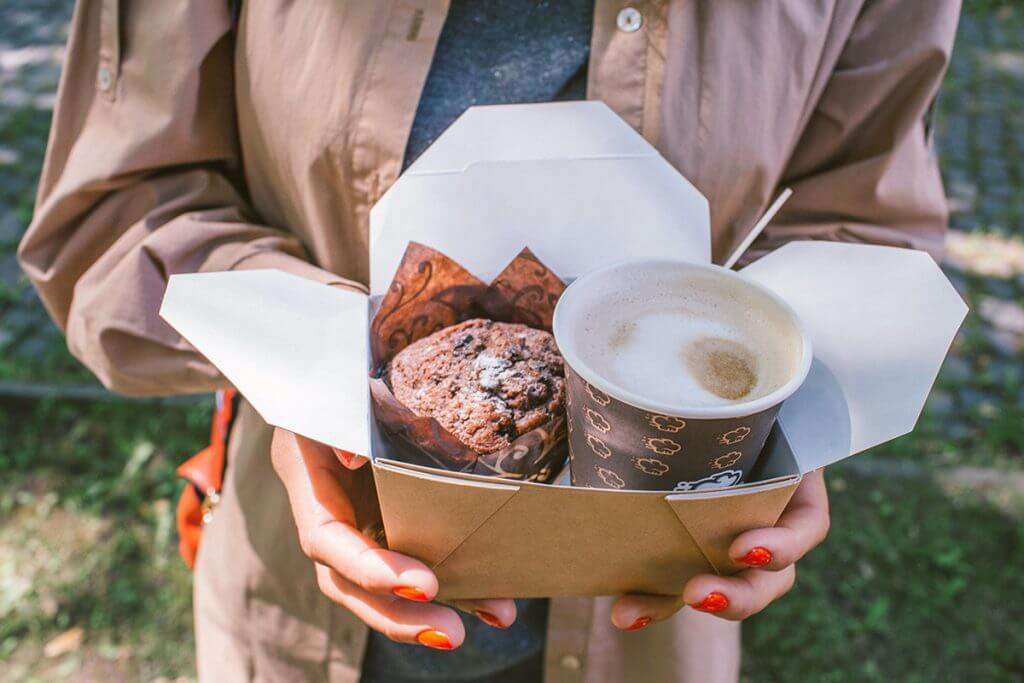 Person holding to-go container with muffin and cup of coffee