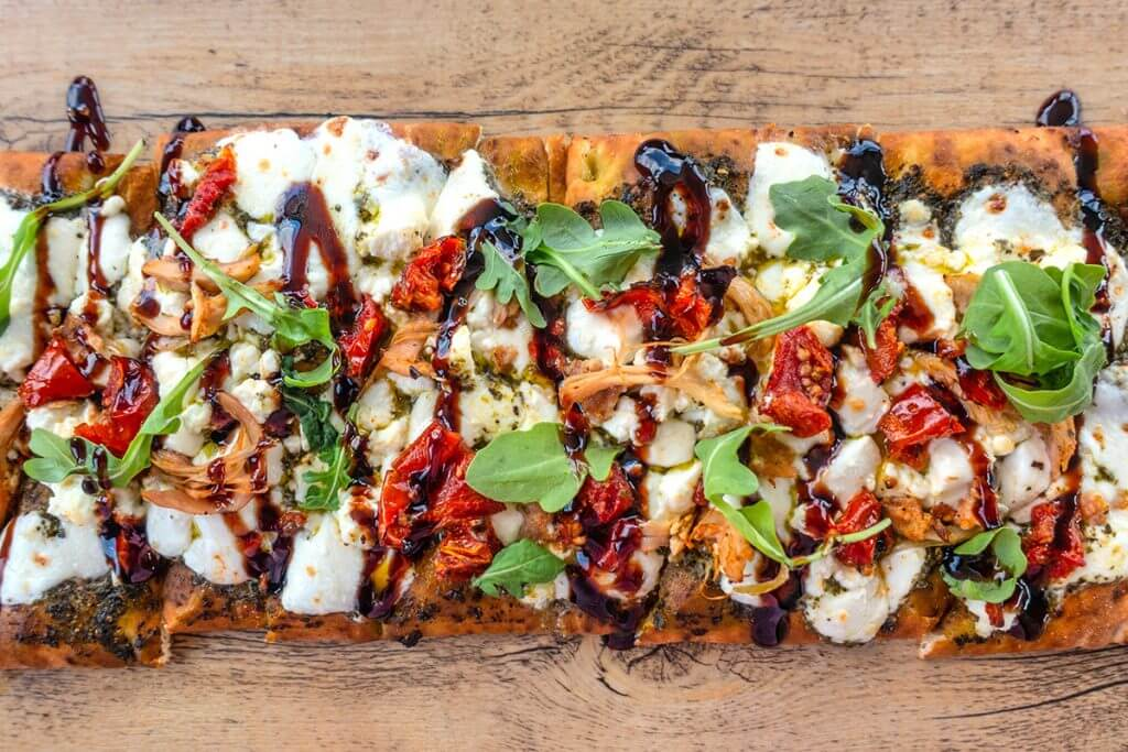 Flatbread pizza sitting on a wooden table