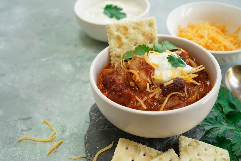 Chili served with crackers, cheese, and sour cream