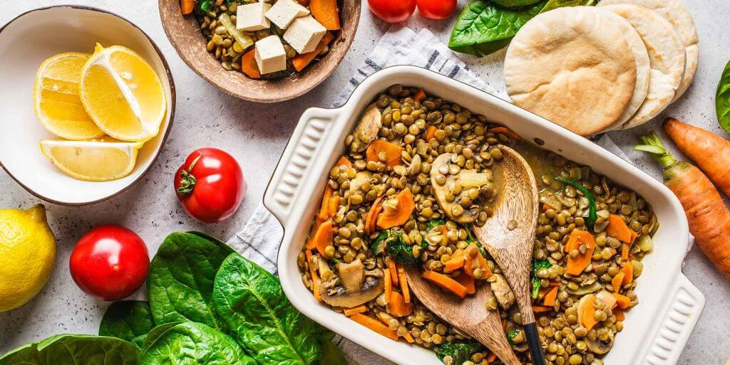 Vegan Lentil Curry in a pan surrounded by bread and various vegetables