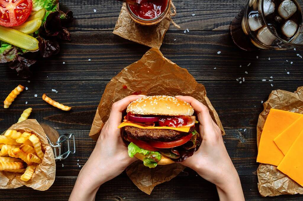 Person holding burger surrounded by cheese slices, soda, ketchup, veggies, and fries