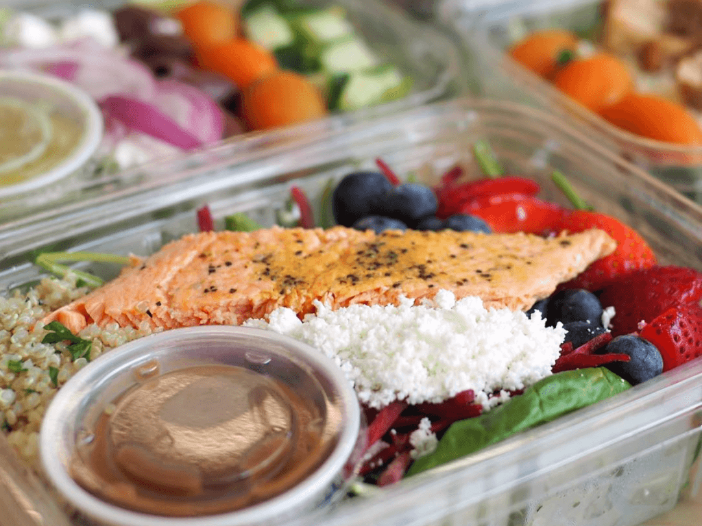 Salmon and berry salad in grab and go containers