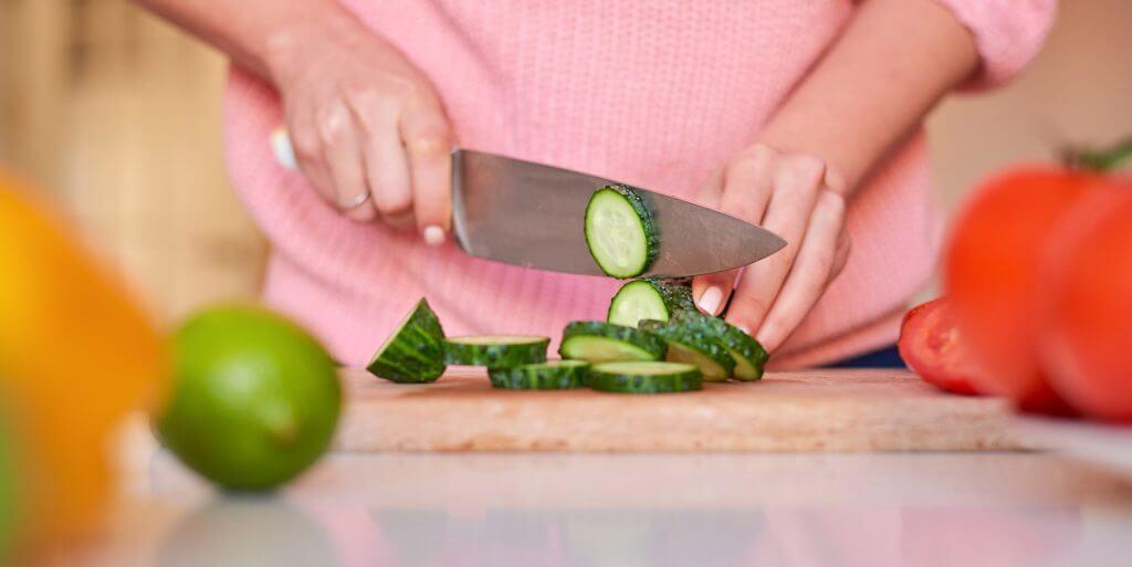Person slicing a cucumber