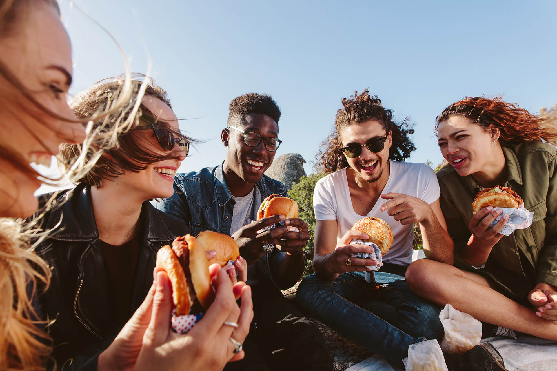 A group of friends enjoying burgers outside