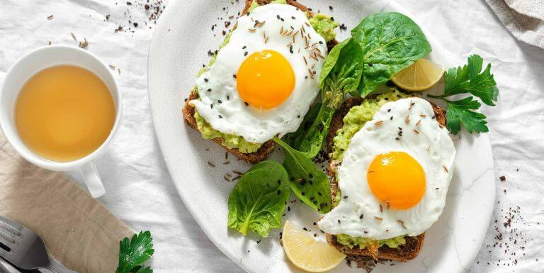 Fried eggs and avocado on toast with tea