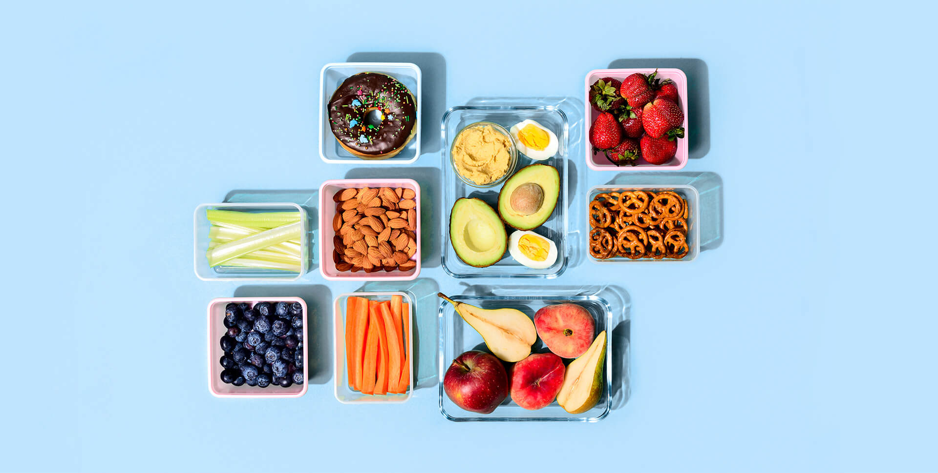 Various types of snacks in reusable containers against a light blue background