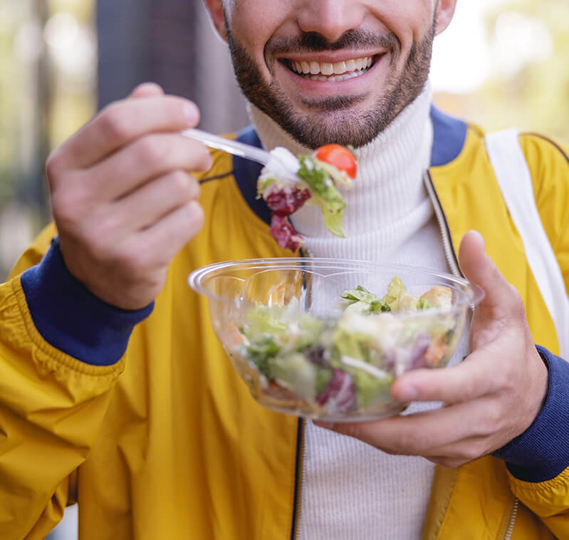 Man smiling while eating a salad