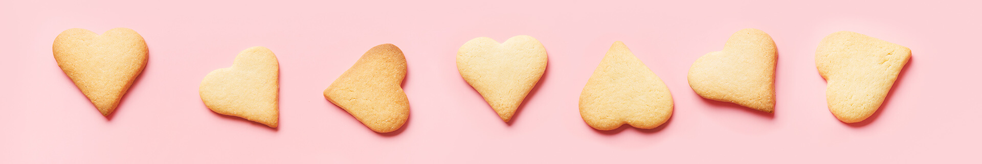 Heart-shaped sugar cookies on pink background