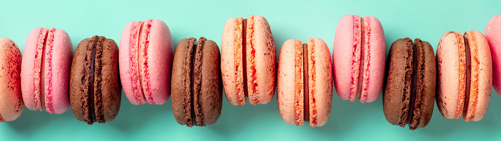 Various macarons on turquoise background