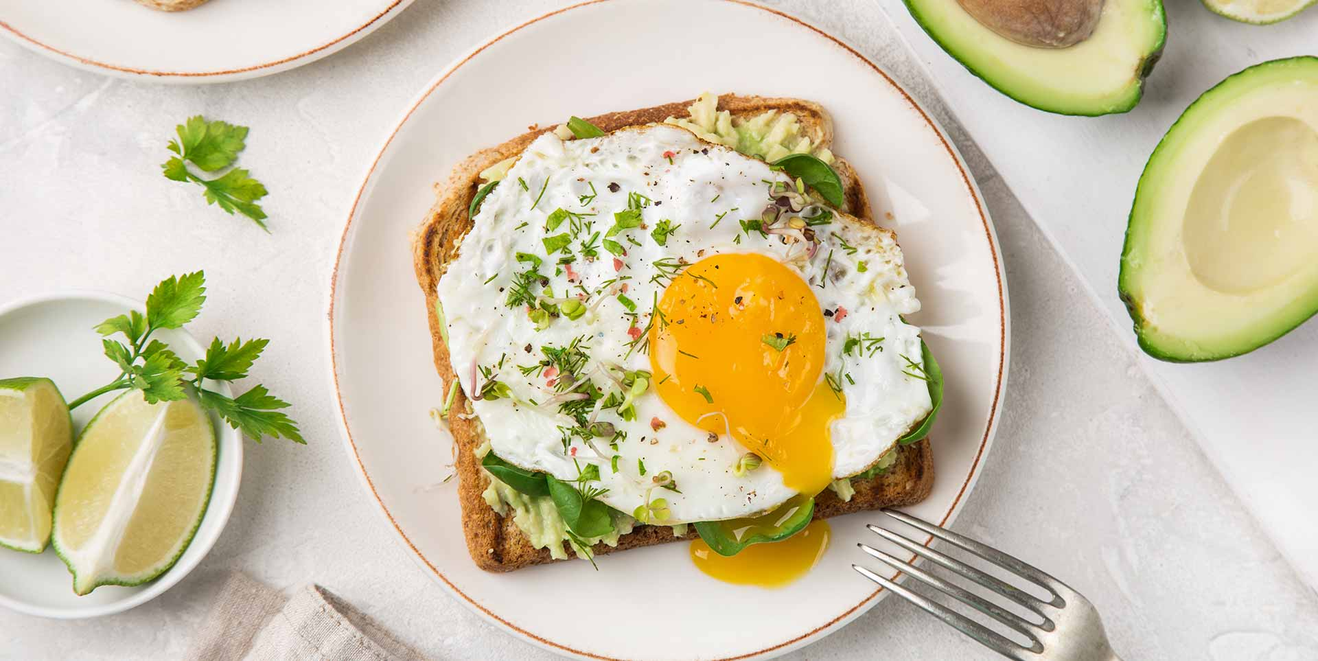 Avocado and egg toast on a glass plate