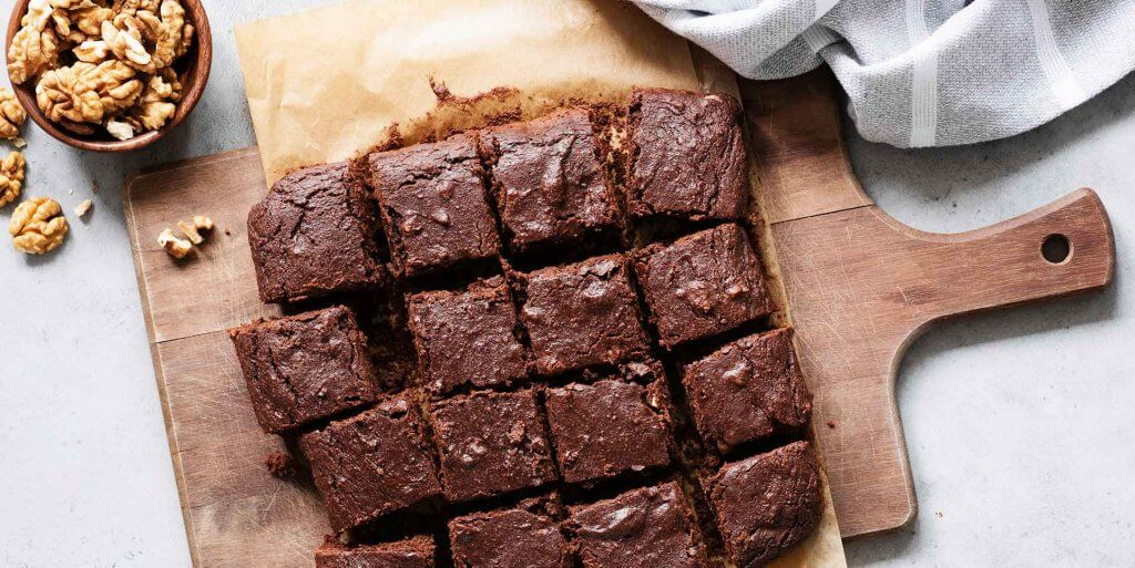 Brownies cut into squares on a wooden cutting board