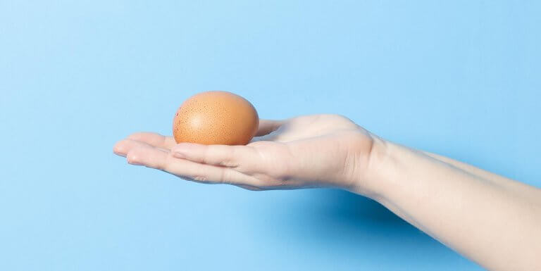 Hand holding a single brown egg against a blue background