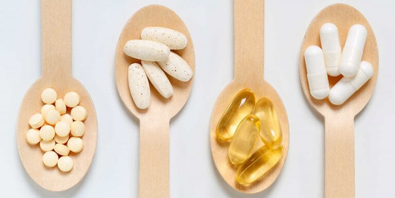 Wooden spoons holding different kinds of vitamins and supplements