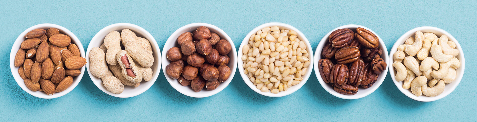 Mixed nuts in small white bowls against a blue background