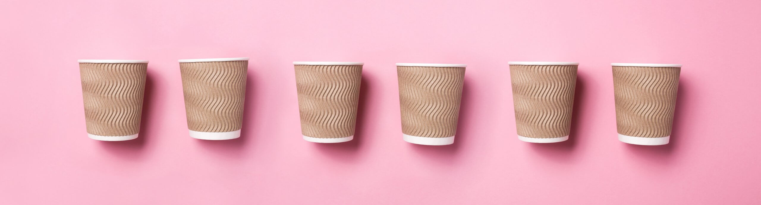 Paper coffee cups on pink background