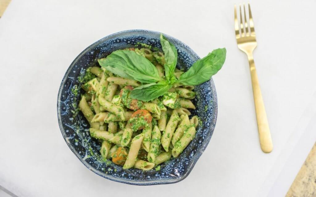 Pesto penne pasta in blue bowl