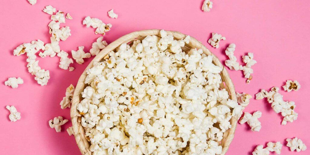 Top-down view of popcorn in a woven basket spilling over onto a pink background