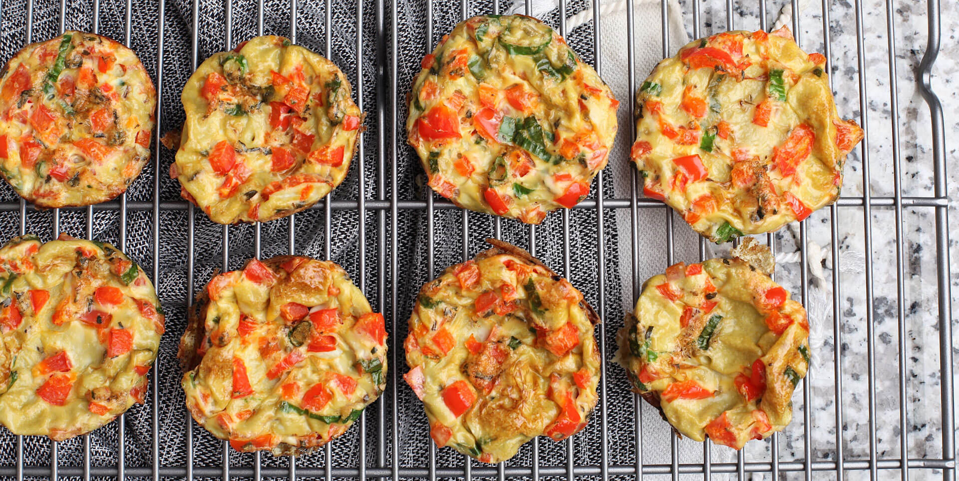 Eight fresh egg muffins cooling on metal tray