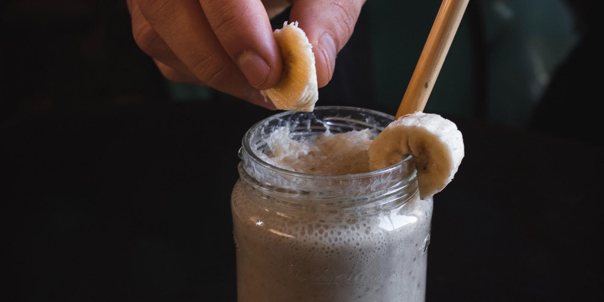 Hand putting banana slice into a Chocolate Banana Smoothie